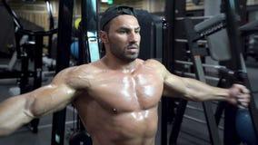 Uomo bello del culturista muscolare con un torso nudo che fa gli esercizi in palestra stock footage