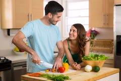 Uomo bello del cuoco unico e bella donna ad una data che taglia le verdure a pezzi e un pasto e un'insalata nutrienti Fotografia Stock