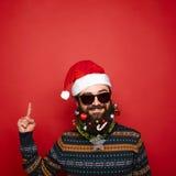 Uomo bello del nuovo anno con la barba decorata che indica su Fotografia Stock Libera da Diritti