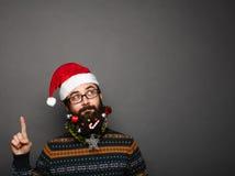 Uomo bello del nuovo anno con la barba decorata che indica verso l'alto Immagine Stock