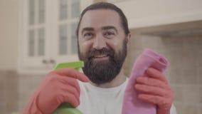 Uomo bello del ritratto con la barba perfetta che sorride e che mostra detersivo dopo la pulizia di tutta la sua casa moderna nuo stock footage