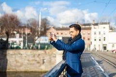 Uomo bello di affari che prende un'immagine con il telefono cellulare all'aperto immagine stock libera da diritti