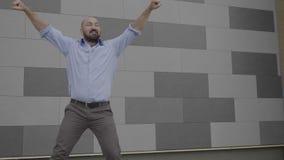 Uomo bello di affari divertenti che getta il suo cappotto e che inizia ballare nel ballo pubblico del latino sulla via - archivi video