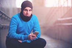 Uomo bello di forma fisica che per mezzo del suo smartphone Fotografia Stock