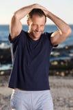 Uomo bello di forma fisica che sorride con le mani dietro la testa Fotografia Stock