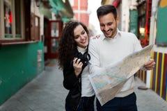 Uomo bello e donna sveglia che esaminano mappa fotografia stock