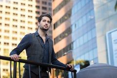 Uomo bello e potente che si appoggia le rotaie del balcone dentro Immagine Stock Libera da Diritti