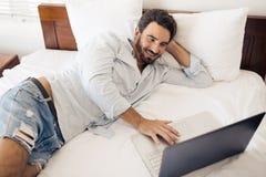 Uomo bello felice che per mezzo del computer portatile Trovandosi sul letto in camera da letto Fotografie Stock
