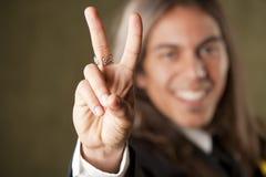 Uomo bello in formalwear facendo un segno di pace Immagini Stock