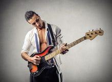 Uomo bello giovane che gioca il basso Immagini Stock Libere da Diritti