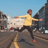 Uomo bello indiano che salta in un contesto urbano Fotografie Stock Libere da Diritti