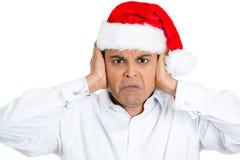 Uomo bello irritato in cappello rosso di natale che chiude le sue orecchie Fotografie Stock Libere da Diritti