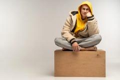Uomo bello in maglia con cappuccio gialla che si siede sul cubo di legno immagini stock libere da diritti