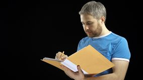 Uomo bello in maglietta blu che guarda attraverso le carte in cartella gialla e nella scrittura Cotract, fatture, concetti della  Fotografie Stock