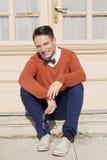 Uomo bello in maglione che si siede sui punti davanti alla casa ed alla p Fotografia Stock Libera da Diritti