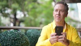 Uomo bello maturo che si siede nella caffetteria mentre per mezzo del telefono cellulare archivi video