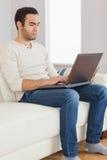 Uomo bello messo a fuoco che per mezzo del suo computer della compressa Immagine Stock Libera da Diritti