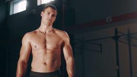 Uomo bello muscolare che sta nella grande palestra video d archivio