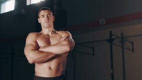 Uomo bello muscolare che sta nella grande palestra archivi video