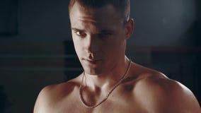 Uomo bello muscolare che sta nella grande palestra stock footage