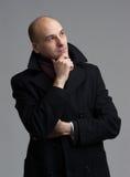 Uomo bello nel pensiero del cappotto fotografia stock