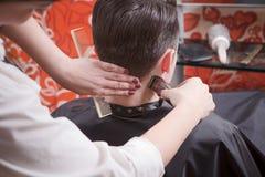 Uomo bello nel salone di lavoro di parrucchiere fotografia stock