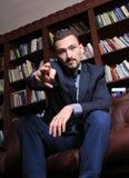 Uomo bello rispettabile accanto ad uno scaffale per libri Immagini Stock