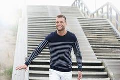 Uomo bello sorridente che cammina giù le scale Immagine Stock