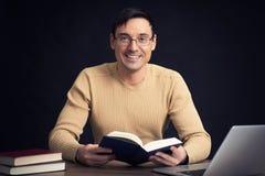 Uomo bello sorridente che legge un libro Fotografia Stock