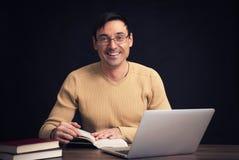 Uomo bello sorridente che legge un libro Immagini Stock Libere da Diritti