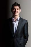 Uomo bello sorridente di affari in vestito su fondo grigio Immagini Stock