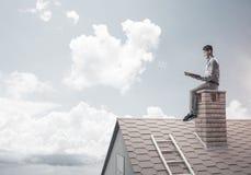 Uomo bello sul tetto del mattone contro il libro di lettura dello scape della nuvola Fotografia Stock
