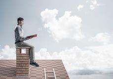 Uomo bello sul tetto del mattone contro il libro di lettura dello scape della nuvola Immagine Stock