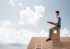 Uomo bello sul tetto del mattone contro il libro di lettura dello scape della nuvola Immagini Stock Libere da Diritti