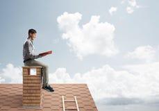 Uomo bello sul tetto del mattone contro il libro di lettura dello scape della nuvola Immagine Stock Libera da Diritti