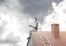 Uomo bello sul tetto del mattone contro il libro di lettura dello scape della nuvola Fotografia Stock Libera da Diritti