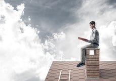 Uomo bello sul tetto del mattone contro il libro di lettura dello scape della nuvola Fotografie Stock Libere da Diritti