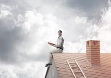 Uomo bello sul tetto del mattone contro il libro di lettura dello scape della nuvola Fotografie Stock