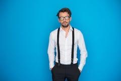 Uomo bello sulla camicia e sui ganci bianchi d'uso del blu immagine stock libera da diritti