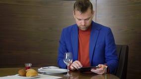Uomo bello sulla tavola in ristorante e nel per mezzo del pc della compressa mentre aspettando l'alimento di ordine stock footage