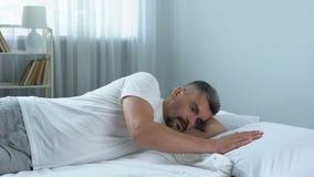 Uomo bello triste che segna delicatamente cuscino accanto lui, solitudine dopo il divorzio stock footage