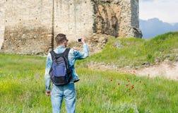 Uomo bello, turista, con lo zaino che prende ad immagini su uno smartphone la fortezza superiore della città della torre di Trigo fotografie stock