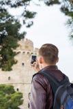 Uomo bello, turista, con lo zaino che prende ad immagini su uno smartphone la torre bianca nel centro Salonicco, la Grecia fotografia stock libera da diritti
