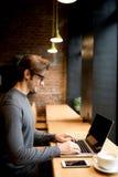 Uomo bello in un caffè con caffè ed il computer portatile Immagini Stock Libere da Diritti