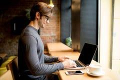 Uomo bello in un caffè con caffè ed il computer portatile Fotografia Stock Libera da Diritti
