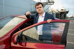 Uomo bello in vestito che pende contro la nuova automobile e che mostra le chiavi Immagine Stock Libera da Diritti