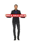 Uomo bello in vestito con il segno di vendita Immagine Stock