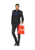 Uomo bello in vestito con il segno di vendita Immagini Stock