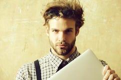 Uomo bello in vetri del nerd sul computer portatile capo della tenuta fotografia stock libera da diritti
