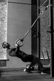 Uomo ben costruito attraente che tiene gli anelli relativi alla ginnastica Fotografie Stock Libere da Diritti